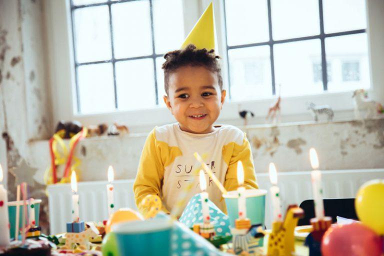 Kind hat Geburtstag und schaut glücklich auf Geburstagskerzen