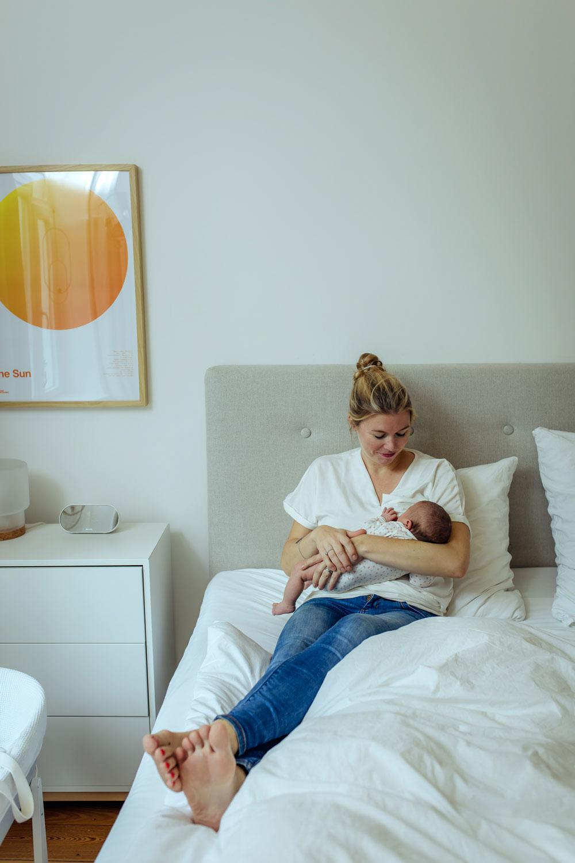 Mutter stillt ihr Kind sitzend im Familienbett