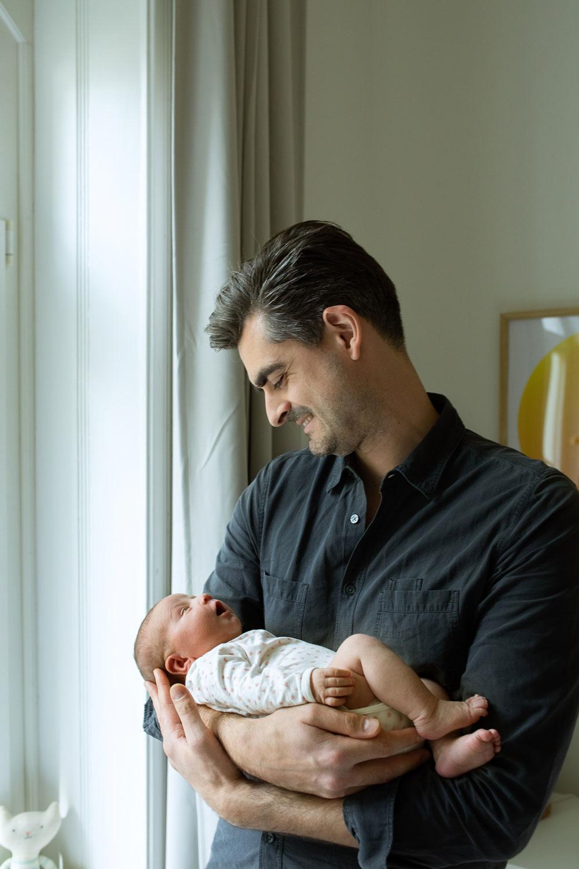Vater hält Baby auf dem Arm und lächelt