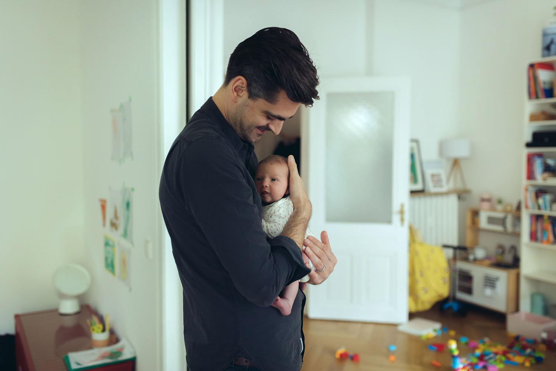 Vater hält Baby schützend auf dem Arm, Wohnzimmer