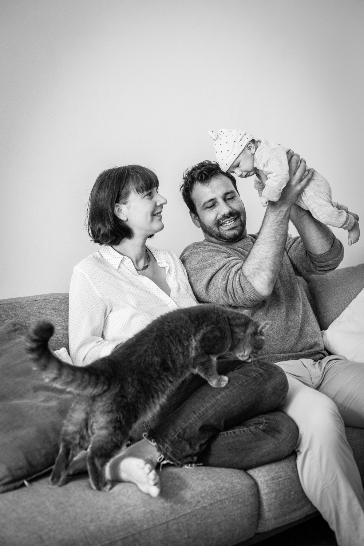 Familie mit Baby und Katze auf Couch