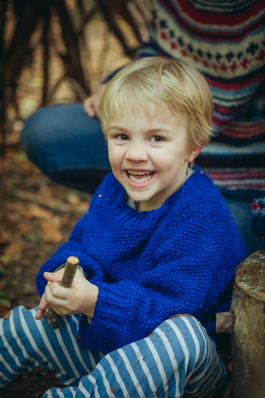 Junge sitzt auf Waldboden und lacht in die Kamera