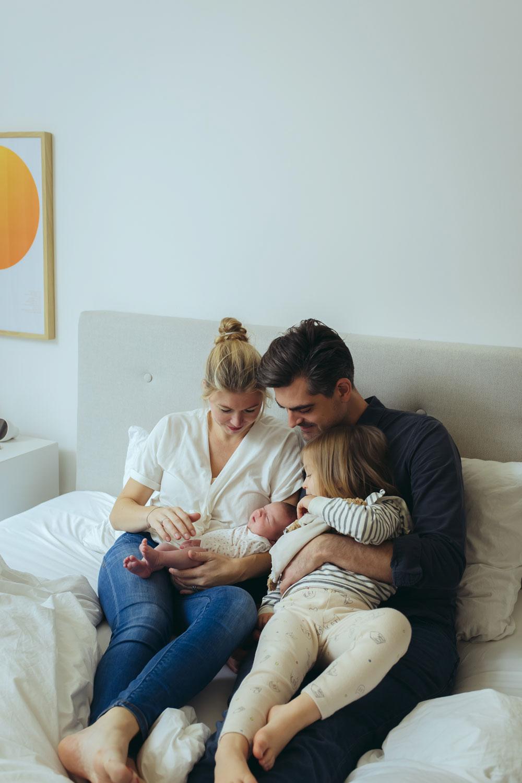 Familie bestaunt ihr Baby im Familienbett