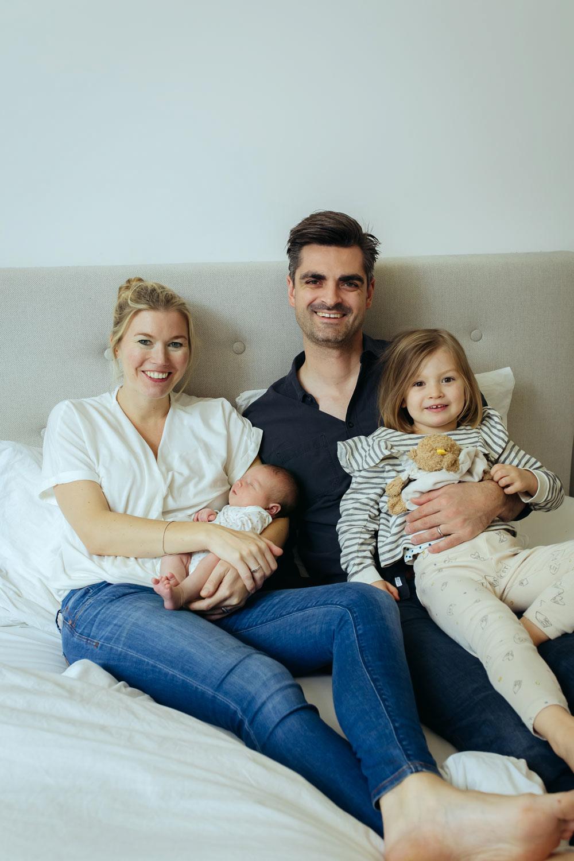 Familie sitzt mit Baby und Tochter im Familienbett