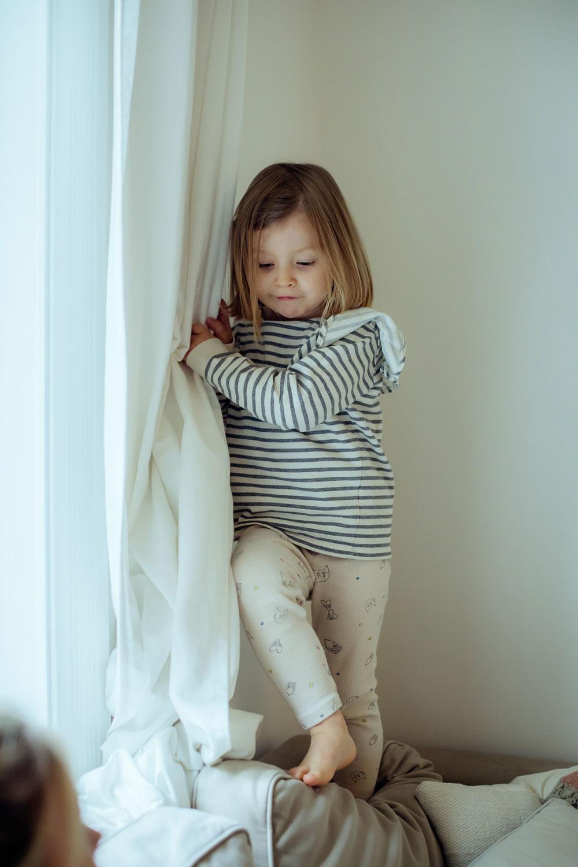 Mädchen klettert aud der Lehne der Couch