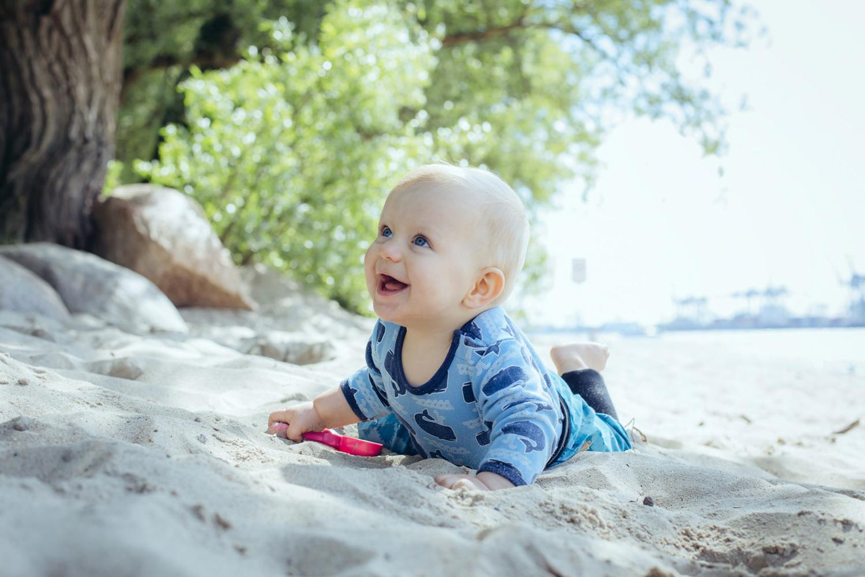 Baby glücklich krabbelnd durch den Sand am Elbstrand
