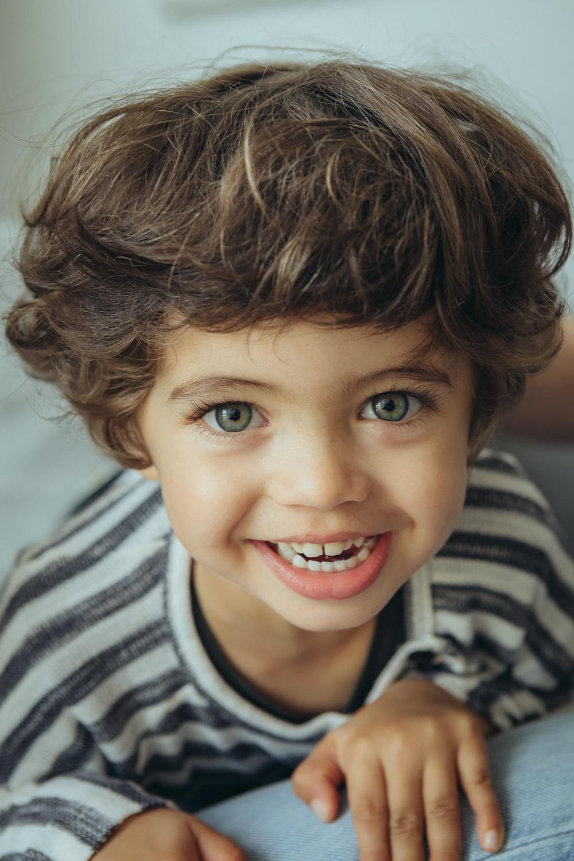 Junge mit Lockenkopf lacht in die Kamera