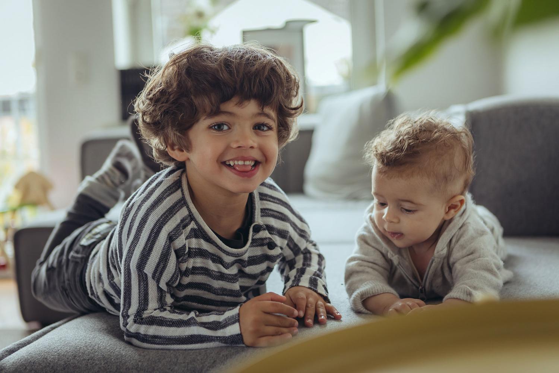 zwei Brüder auf Couch, großes Kind lacht in die Kamera