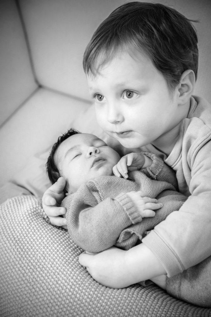 Junge hält Geschwisterchen im Arm
