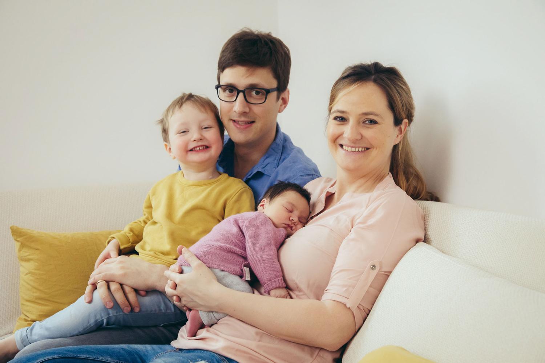 Familie sitzt zu viert auf Couch und lacht in die Kamera