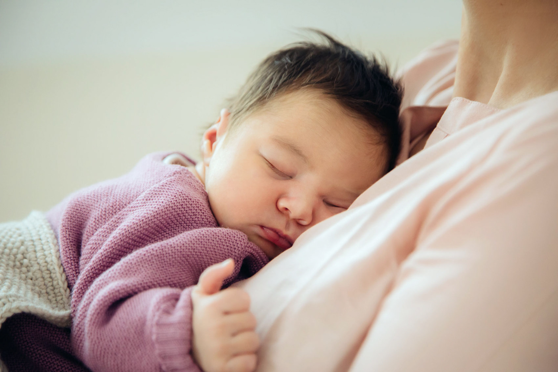 Baby bei Mama auf der Brust eingeschlafen