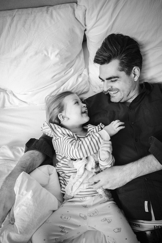 Vater und Tochter lachend und tobend im Familienbett
