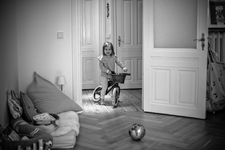 Mädchen fährt mit Laufrad durch die Wohnung