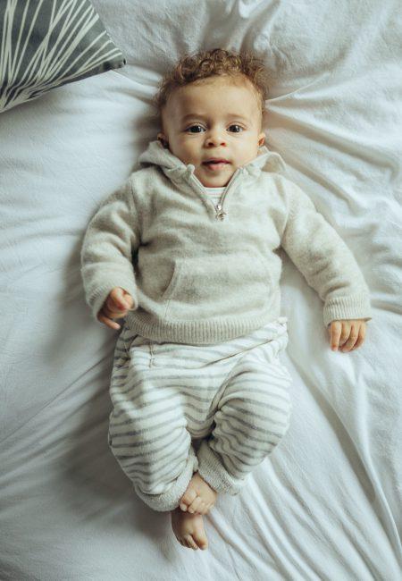 Baby in heller Kleidung auf Familienbett