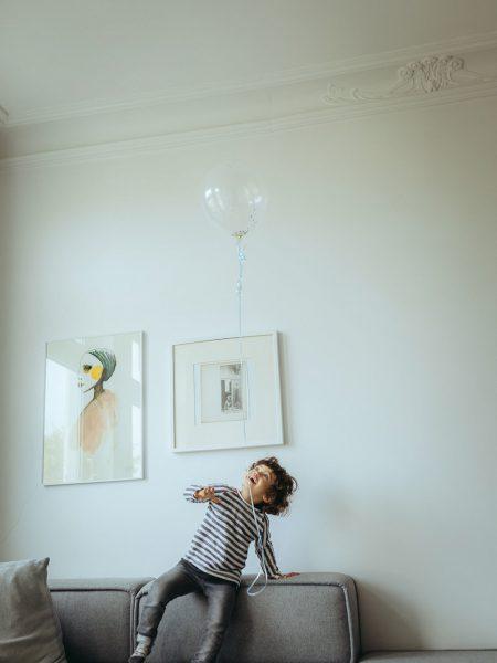 Kind spielt mit Luftballon im Wohnzimmer auf Couch